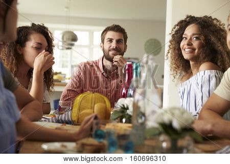 Young adult friends sitting at a table for lunch, close up