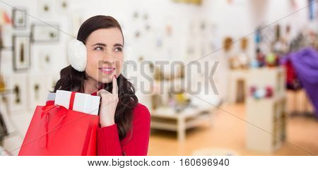 Brunette with ear muffs holding shopping bag full of gifts against furniture and design store