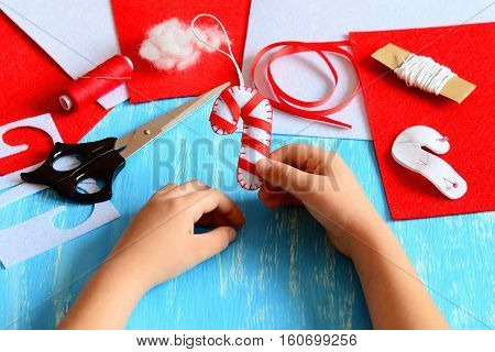 Small child holds Christmas felt candy cane in his hands. Child made a felt candy cane. Sewing supplies to create Christmas tree decorations. Easy kids activity. Kids Christmas art idea. Closeup