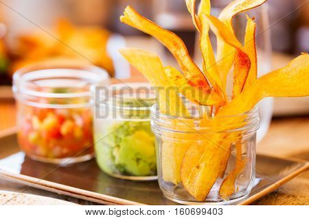 crunchy plantain chips served in glass jar with salsa and guacamole snack or appetizer delicious and colorful