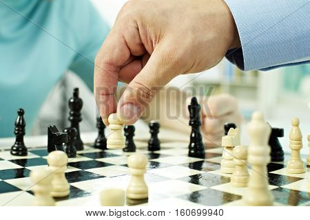 Close-up of a male hand moving a chess pawn