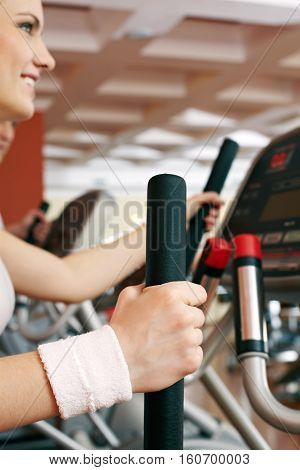 Close-up of levers of exercise machine and a girl working out with it