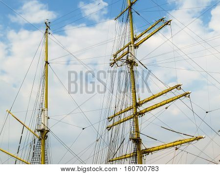 Masts of the ancient sailing ship on the blue sky background