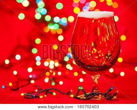 Full snifter glass of pale lager of pilsner beer with christmas lights on red background