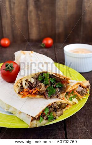 Shawarma sandwich - fresh roll of thin lavash (pita bread) filled with grilled meat mushrooms cheese cabbage carrots sauce green. Traditional Eastern snack. On a dark wooden background.