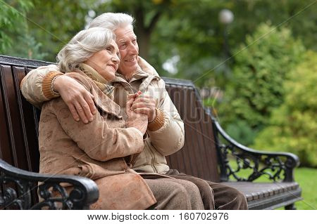 Portrait of a happy elderly couple sitting on a bench in autumn park
