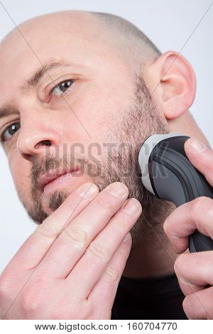 closeup of a man shaving his beard off with an electric shaver