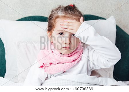 Sick kid lying in the bed and touch her forehaed