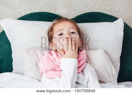 Sick little girl coughing in a bed