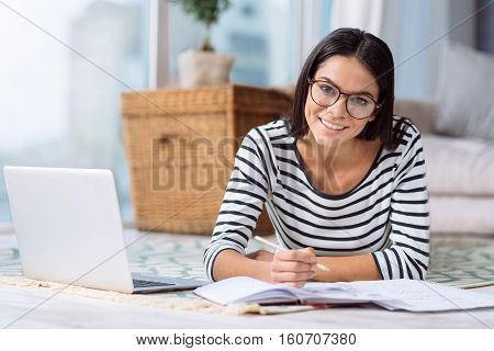 I enjoy creating the project. Pleasant positive charming woman lying on the floor at home in front of the laptop while expressing involvement in the process of creating the project and making notes