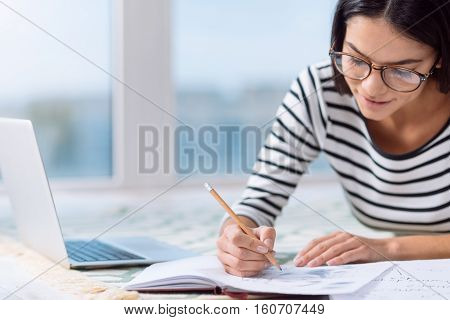I enjoy studying at home. Involved positive delighted woman sitting at home in front of the laptop while expressing involvement in the process of studying and making notes