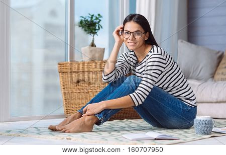 Happy from having free time. Charming delighted young woman sitting on the floor at home while expressing happiness and enjoying her free time