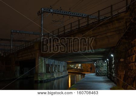 Night evening photograph of the railway bridge as it crosses the Leeds and Liverpool canal at Granary Wharf