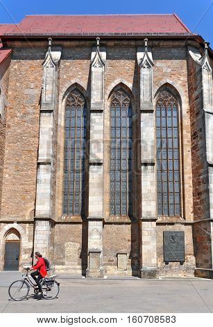 Kirchheim Teck, Germany - April 20, 2016: Side facade of the old Gothic church with buttresses. Woman on bicycle in the foreground. Baden-Wurttemberg, Germany.