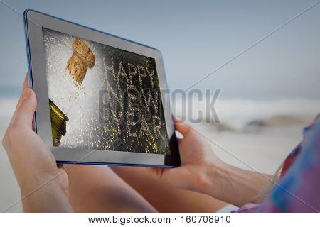 Woman sitting on beach in deck chair using tablet pc against close up of champagne cork popping