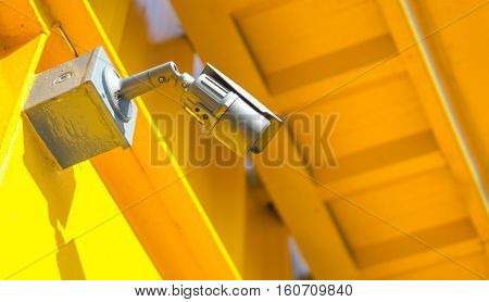 Security camera equipment concept - Black color CCTV camera surveillance on wall of yellow home or tower Safety system area control and copy space
