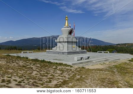 View of  Buddhist stupa Sofia in the Retreat Center Plana - Diamondway Buddhism Bulgaria near by Vitosha, Rila, Pirin, and Balkan mountains  from  distance