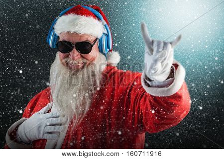 Santa claus showing horn sign while listening to music on headphones against snowflake pattern