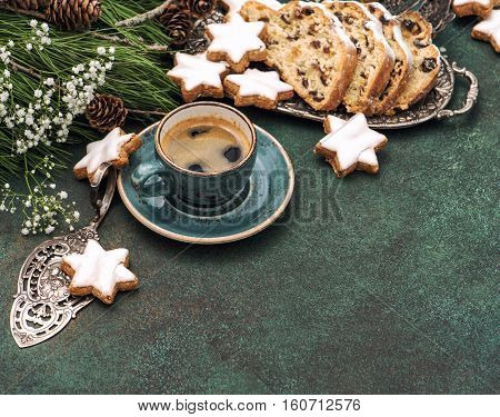 Traditional Christmas Stollen cookies coffee and decoration. Holidays food. Vintage style toned picture