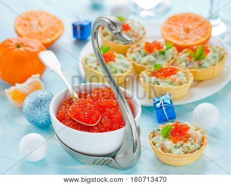 Festive Christmas table with refreshments - red caviar in a bowl tartlets stuffed with salmon salad and red caviar luxurious delicacy appetizer and holiday decorations. New Year party food