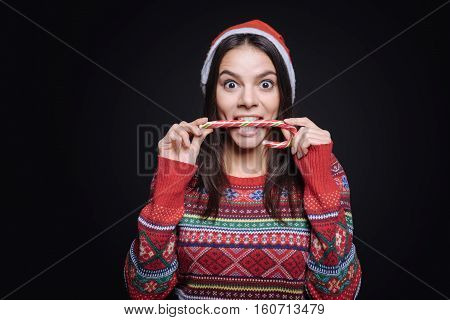 Delicious dessert. Surprised amused joyful girl standing isolated in black background and expressing joy while eating the candy stick