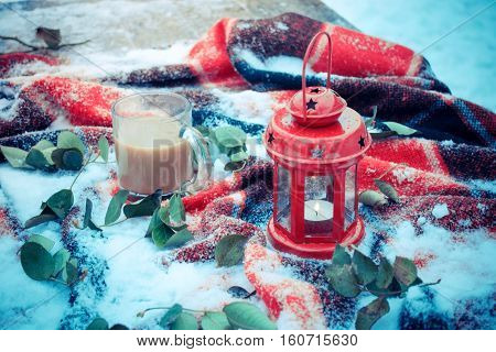 Festive red candle in a lantern and a mug of coffee on a red rug with snow with green leaves. Winter snow Christmas New Year holiday background snowy winter filter