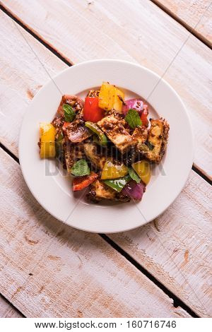 Spicy Paneer or chilli paneer or cottage cheese, served in white Dish with capsicum and onion, favourite indian starter menu, selective focus