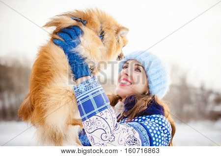 Smiling Woman Holding Her Pet Dog In His Hands Near Face, Overhead. Spitz Breed Dog Playing With A W