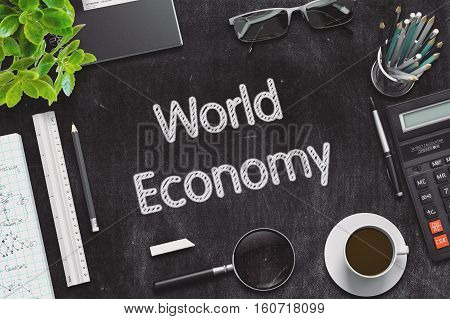 World Economy - Black Chalkboard with Hand Drawn Text and Stationery. Top View. 3d Rendering. Toned Illustration.