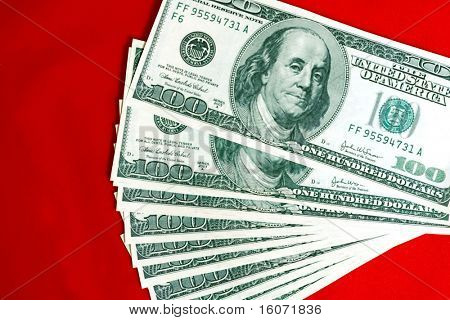 Photo of a $100 banknotes isolated on red