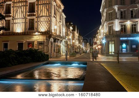 Night view of the fountain and street in the center of Troyes in France
