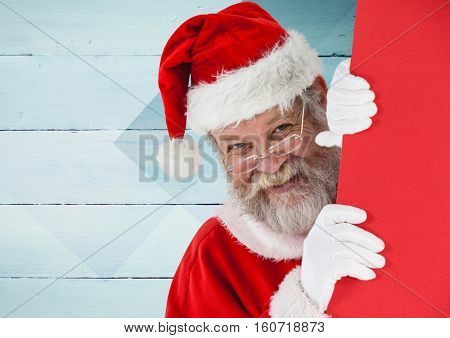 Santa peeking out from behind the wall against wooden background