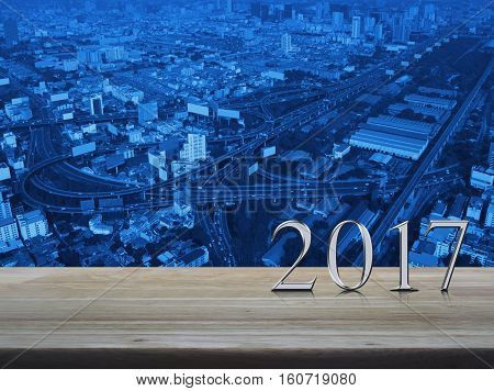 Happy new year 2017 silver metal text on wooden table over aerial of modern city tower street and expressway