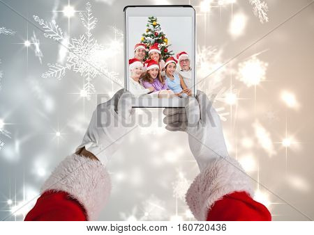 Santa holding a digital tablet with photo of christmas family against digitally generated christmas background