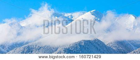 travel ski resort background with ski slopes panoramic view, snow mountain peak, fog and blue sky