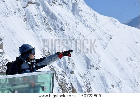 Skier Woman In Ski Clothes And Ski Googles Pointing The Direction