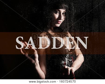sadden written on virtual screen. hand of young woman melancholy and sad at the window in the rain