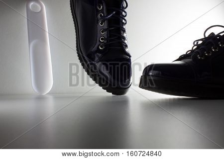 Blue, patent leather shoes with laces and a white spoon for footwear on a white background.