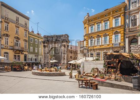 Pula, Croatia-10 June, 2016. Ancient Roman triumphal arch or Golden Gate and square decorated for the Days of Antiquity - Pula Svperiorvm on 10 June, 2016 in Pula, Croatia.