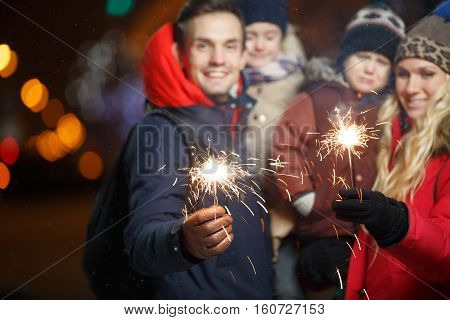 Smiling family with sparklers in park at night in new year