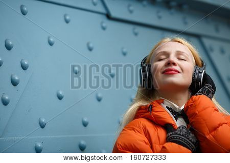 Woman with pleasure listens to music on headphones at blue wall