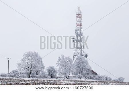 Transmission tower in winter Telecommunications tower with cellular antenna and satellite dish