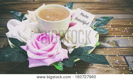 Rose Flowers On A Plate On A Wooden Table, A Note On The Paper