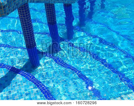 The pool is revetted with a blue tile and filled with clear water