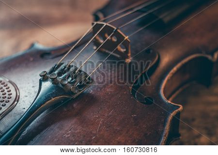 Old violin on a wooden background stringed musical instrument in close-up