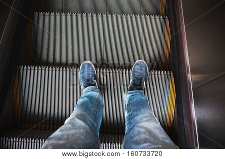 Feet In Sneakers Stand On Escalator