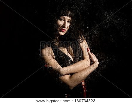 black widow in a veil, mysterious sad woman wearing lace. posing behind transparent glass covered by water drops.