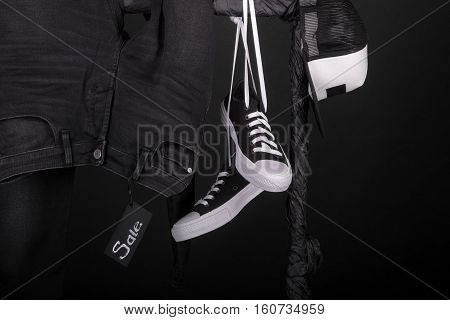 Sale Sign. Black And White Snakers, Cap  Pant, Jeans Hanging On Clothes Rack   Background.   Friday.