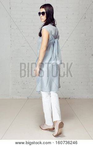 Nice and style girl image making in studio. She is staying turned in profile in studio with brick walls. She walks away from the photographer