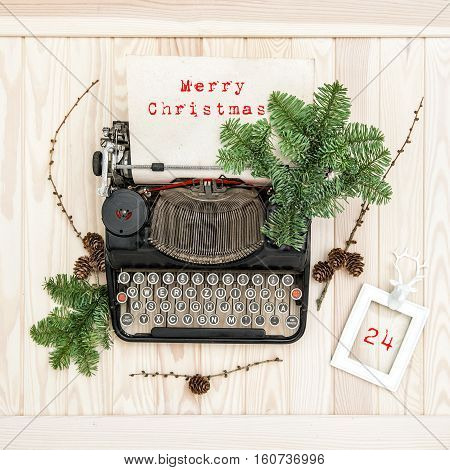 Vintage typewriter with Merry Christmas! christmas decoration evergreen tree brunches pine cones and picture frame